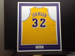 Basketball jersey of Magic Johnson framed with purple mat and engraved plate added at bottom.